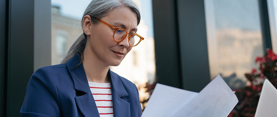 Middle aged woman looking thoughtfully at papers.