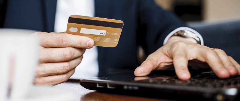 Man holding his credit card while typing on a laptop